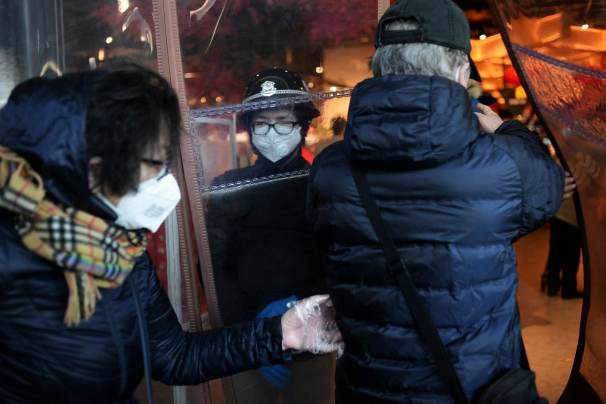 Customers entering a 7Fresh supermarket outlet in Yizhuang, Beijing, on Feb 8, 2020, as a security worker stands guard.
