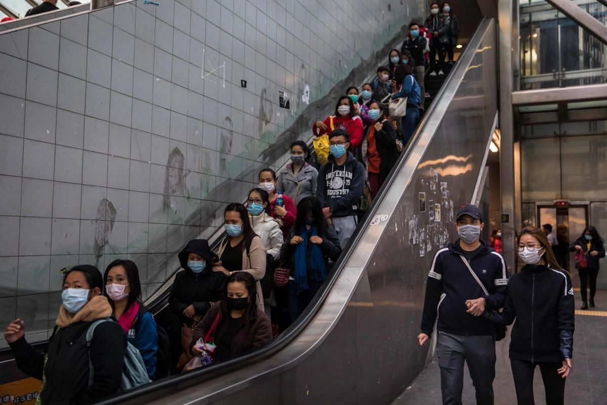 People with face masks at an escalator in Hong Kong on Feb 9, 2020.
