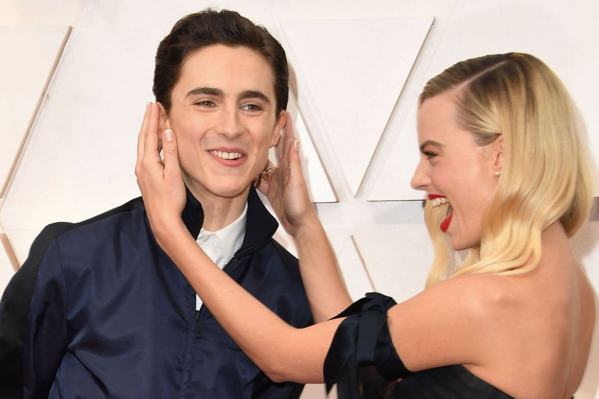 Australian actress Margot Robbie playing with US-French actor Timothee Chalamet as they arrive for the 92nd Oscars at the Dolby Theatre in Hollywood on Feb 9, 2020.