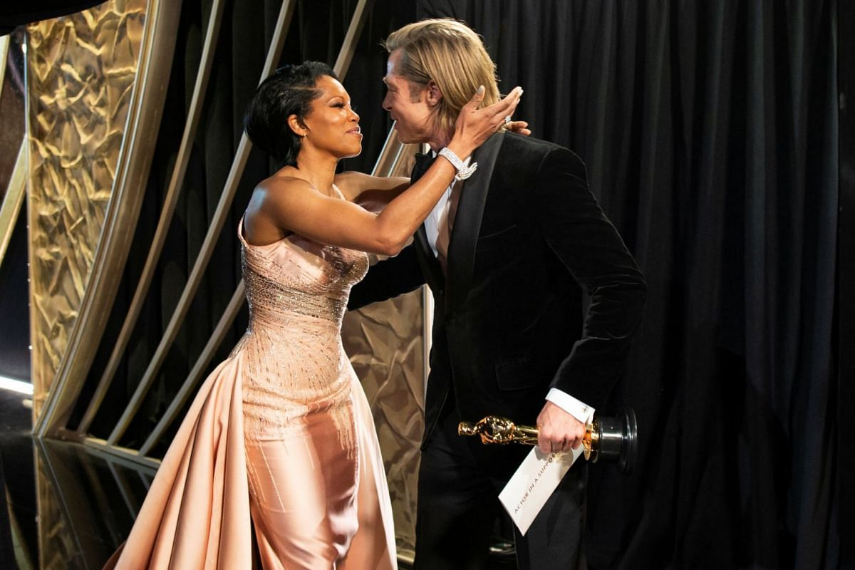 Brad Pitt holds the Oscar for Best Supporting Actor in Once Upon A Time In Hollywood as he embraces Regina King.