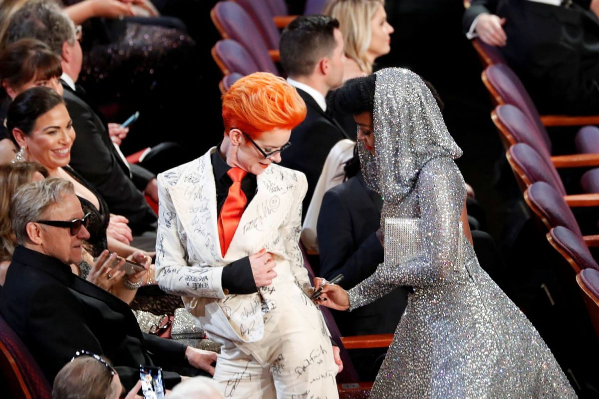American singer-songwriter Janelle Monae signing British costume designer Sandy Powell's outfit during the Oscars show on Feb 9, 2020.