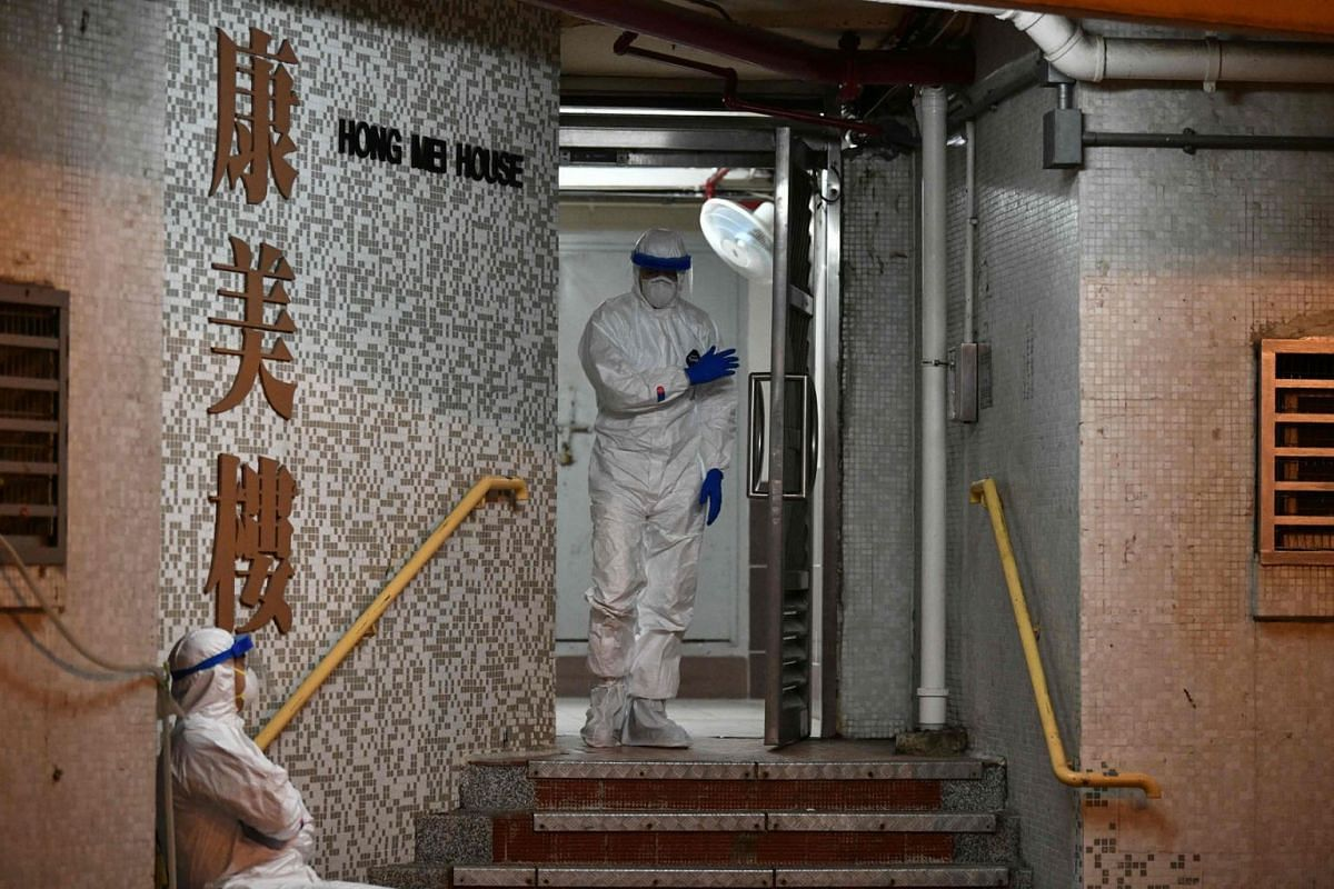 Medical personnels wearing protective suits wait near a block's entrance in the ground of a residential estate, in Hong Kong, early on February 11, 2020, after two people in the block were confirmed to have contracted the coronavirus according to loc