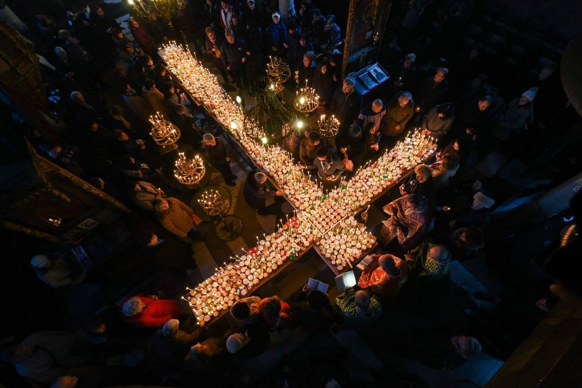 Believers attend a ceremony marking the day of Saint Haralampi, protector of beekeepers, around a cross-shaped platform covered with candles placed in jars of honey, at the Church of the Blessed Virgin in Blagoevgrad, on February 10, 2020. PHOTO: AFP