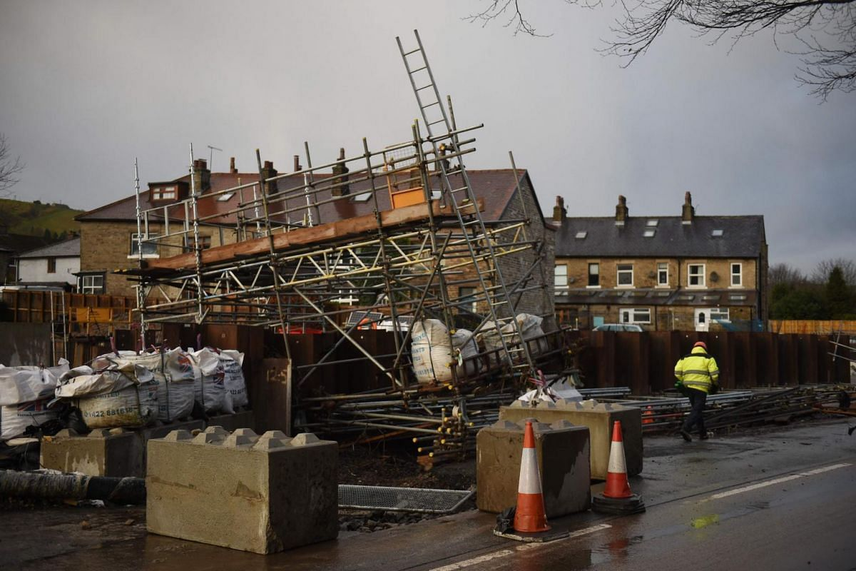 A man walks by fallen scaffolding after flooding and high winds brought by Storm Ciara in Mytholmroyd, England, on Feb 10, 2020.