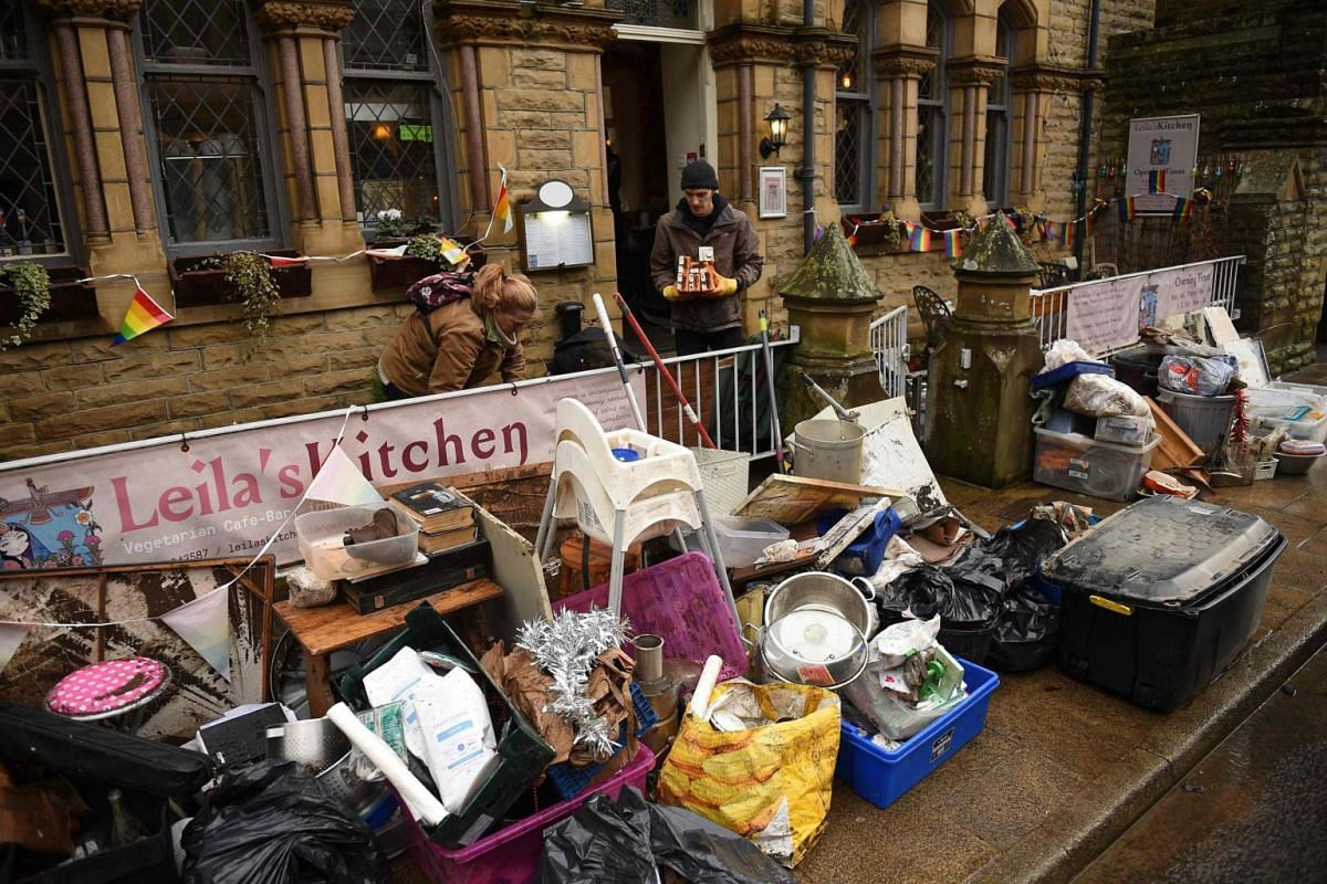 People help to clear up at a business after flooding brought by Storm Ciara, in Hebden Bridge, England, on Feb 10, 2020.