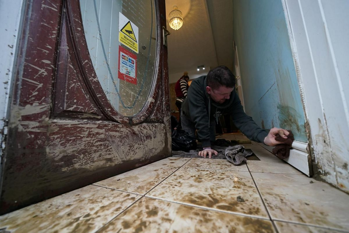 Matthew Bartlett cleans up the Beauty Bliss salon after floodwaters hit Llanrwst in North Wales, on Feb 10, 2020.