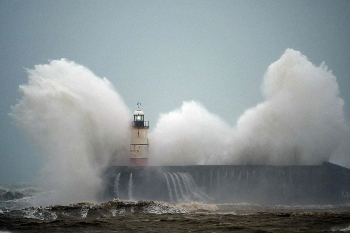 Waves crash over Newhaven Lighthouse on the south coast of England on Feb 9, 2020.