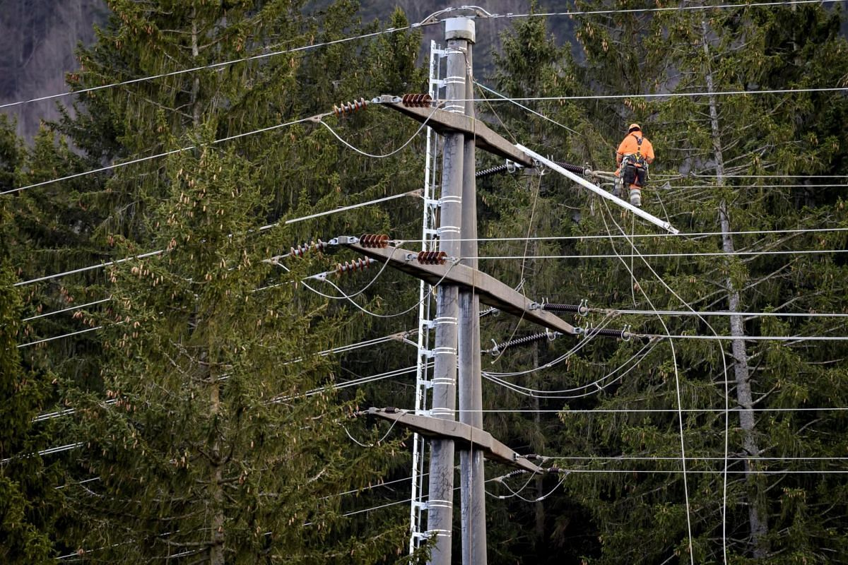 A person repairs power lines after Storm Ciara hit Reconvilier, Switzerland, on Feb 10, 2020.