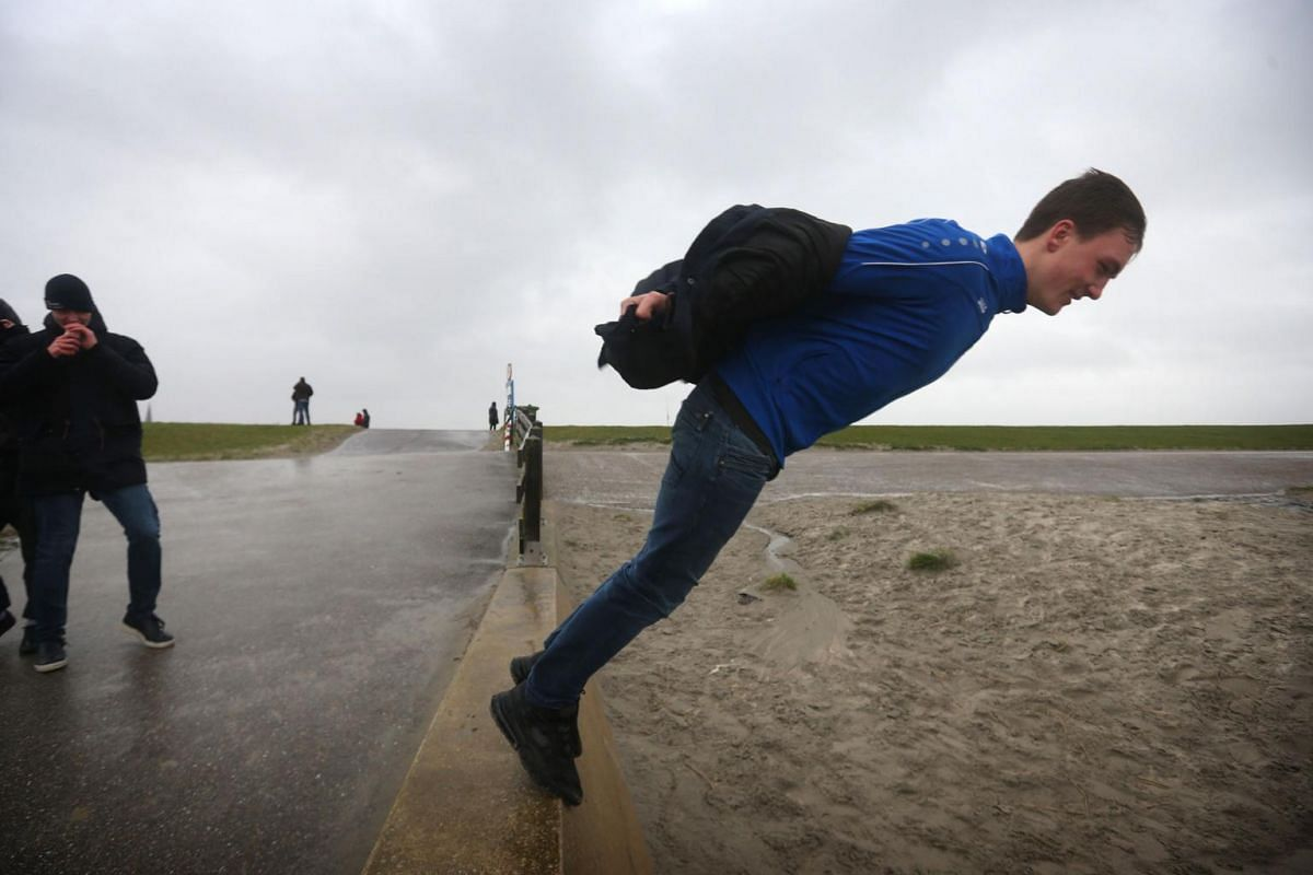 A man leans into the wind on the edge of a seawall during Storm Ciara in Harlingen, the Netherlands, on Feb 9, 2020.
