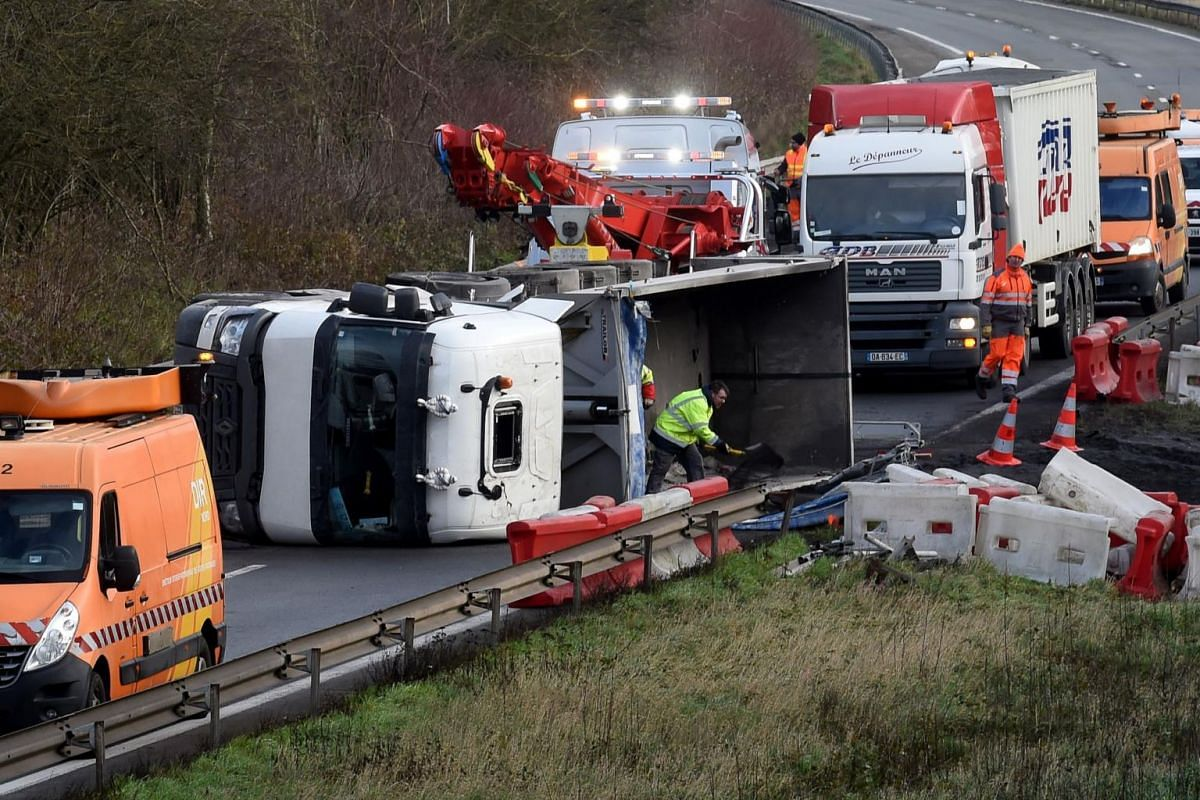 Rescuers work on the A2 motorway after a truck was tipped over in the early morning from strong winds brought by Storm Ciara in Marly, northern France, on Feb 10, 2020.