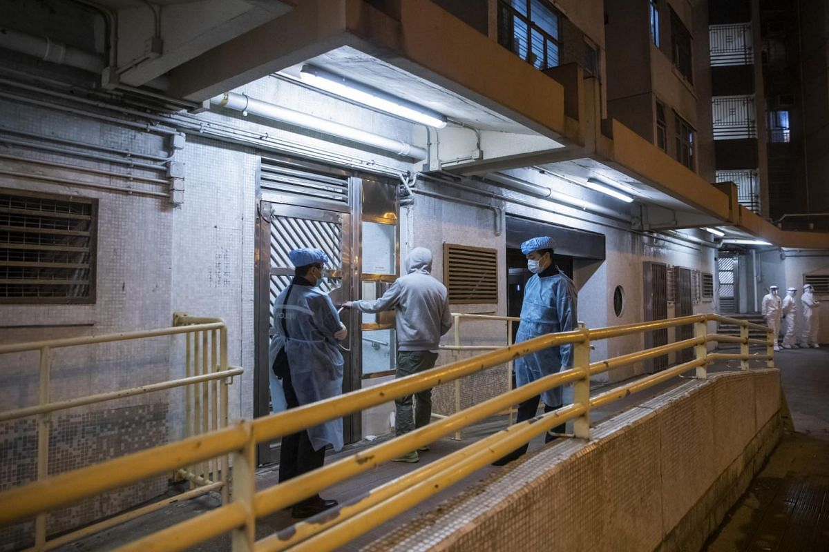 Police officers wearing protective gear stand guard as a resident enters the Hong Mei House residential building at Cheung Hong Estate in Hong Kong on Feb 11, 2020.