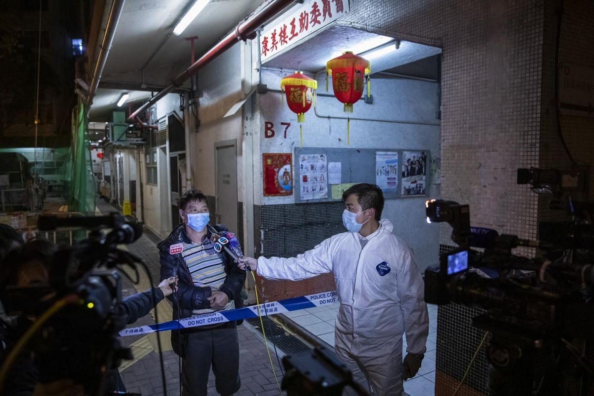 A member of the media wearing protective gear interviews a man outside the Hong Mei House residential building at Cheung Hong Estate in Hong Kong on the morning of Feb 11, 2020.