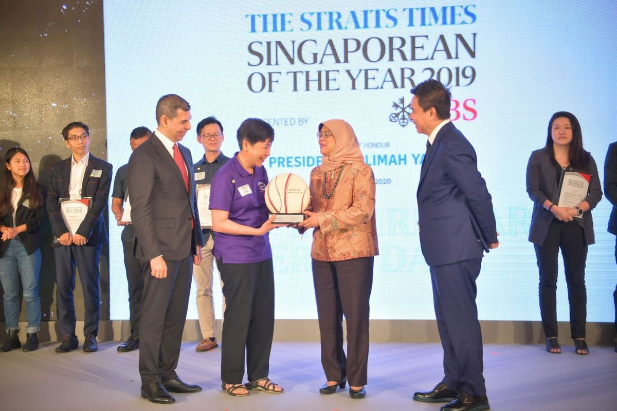 President Halimah Yacob presenting The Straits Times Singaporean of the Year 2019 award to Brahm Centre founder Angie Chew, 56, on Feb 11, 2020. Looking on are Mr Warren Fernandez (far left), editor-in-chief of Singapore Press Holdings' English/Mal