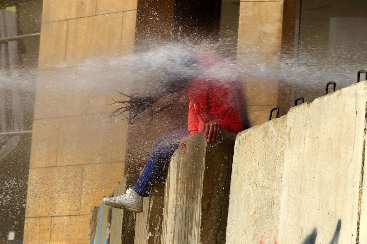 A Lebanese Protester is hit with a burst from a water cannon during clashes with army soldiers on February 11, 2020, as demonstrators gather in the heart of Beirut to stop a confidence vote for a new government, which they say fails to address their