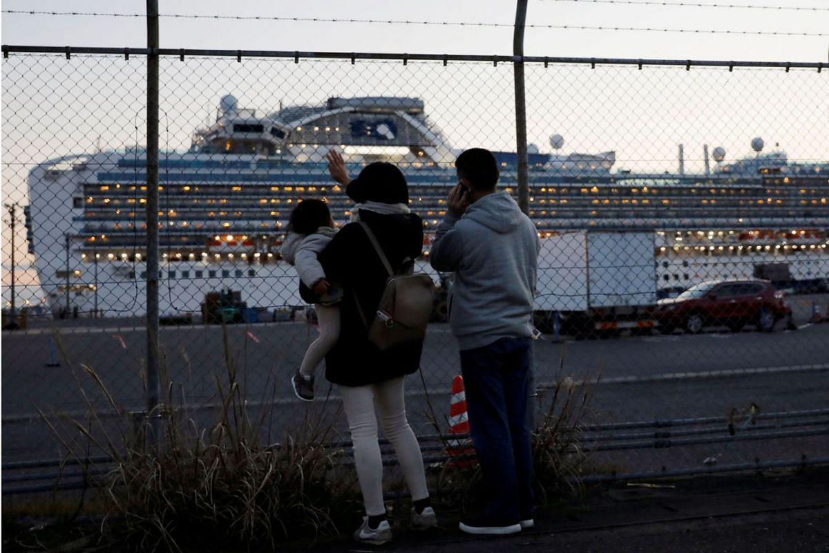 Family members of passengers onboard the cruise ship Diamond Princess, where dozens of passengers were tested positive for coronavirus, wave and talk to them on the phone at Daikoku Pier Cruise Terminal in Yokohama, Japan February 11, 2020. PHOTO: RE
