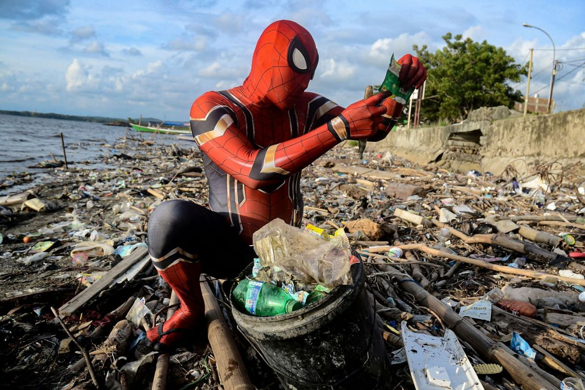 A photo released on Feb 12, 2020, shows Rudi Hartono dressed in a Spiderman costume looking at plastic waste as he collects rubbish at a beach in Pare-Pare, South Sulawesi province, Indonesia on January 18, 2020. PHOTO: REUTERS