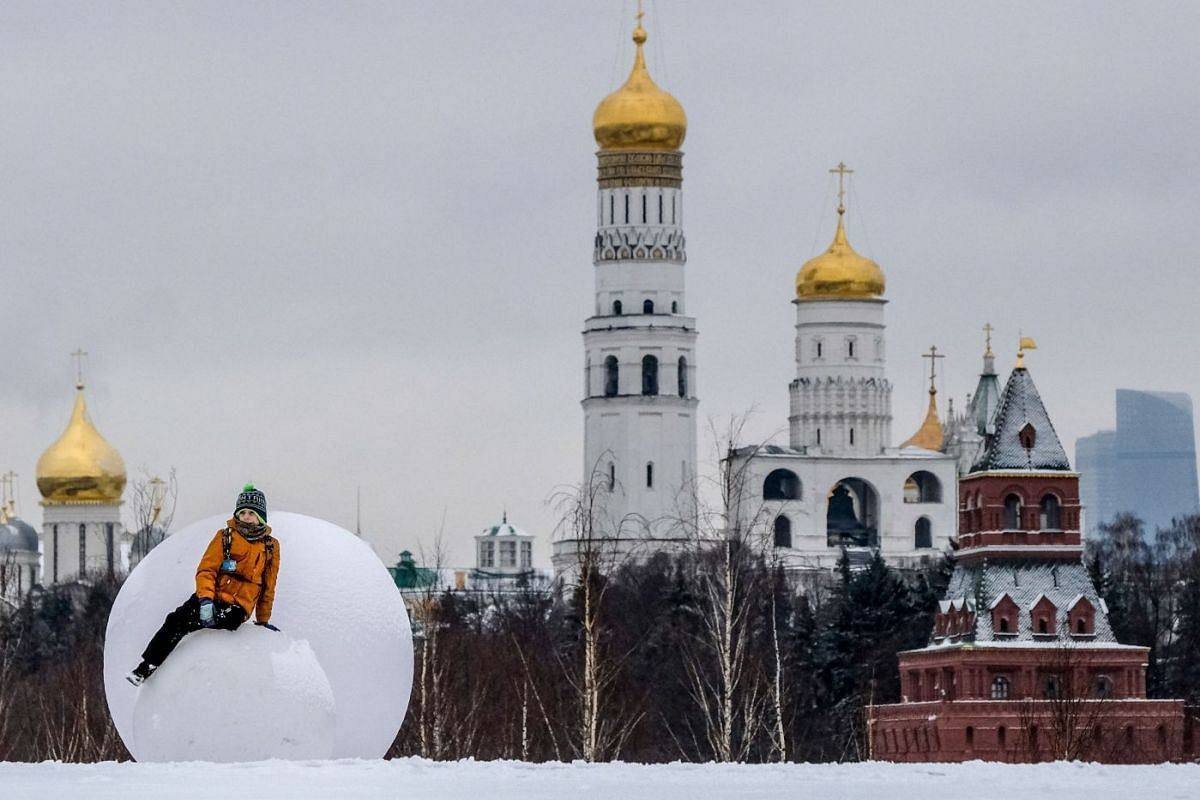 A boy plays on an art installation featuring snowballs at the Zaryadye park, with the Kremlin's cathedrals, towers and Ivan the Great bell tower seen in the background, in downtown Moscow on February 11, 2020. PHOTO: AFP