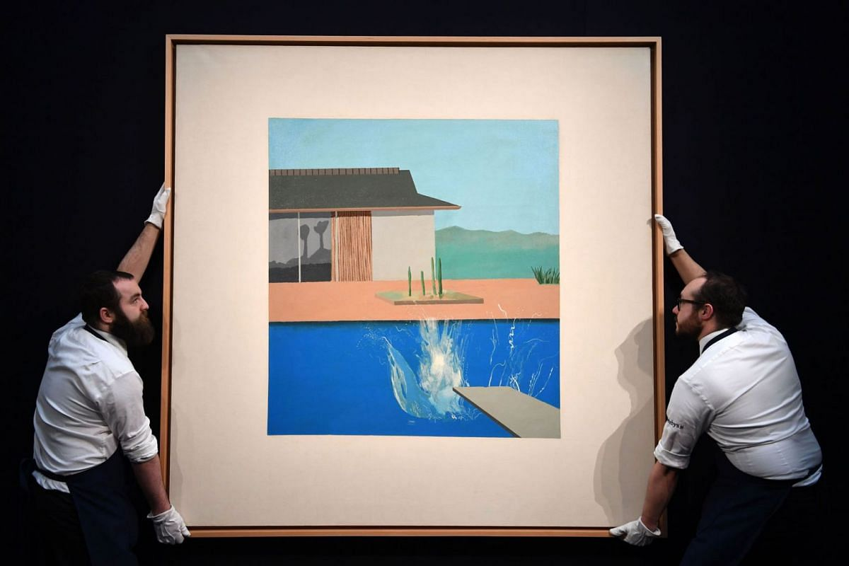 """A photo taken on February 7, 2020 shows gallery assistants beside an artwork entitled 'The Splash' 1966, by British artist David Hockney, during a photo call at Sotheby's Galleries in central London. Seminal pop art painting """"The Splash"""" by David Hoc"""