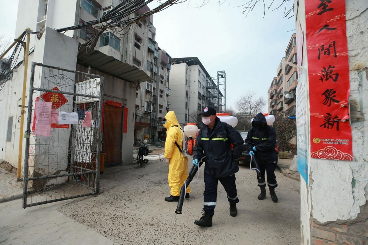 Workers with sanitising equipment  on Feb 12, 2020, disinfecting a residential compound in Kaifeng, Henan province, following an outbreak of the coronavirus in China.
