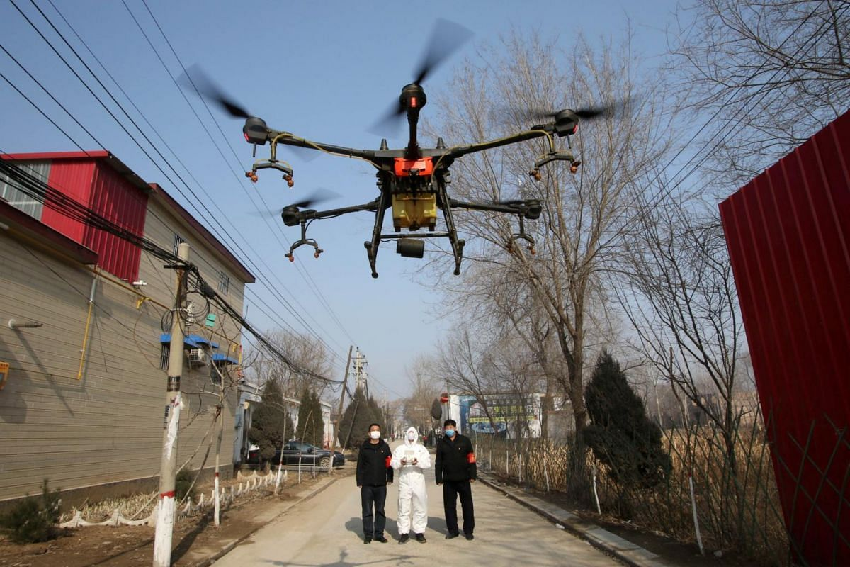 A volunteer in protective gear controlling a drone to spray disinfectant in a village in Hebei province, China, on Jan 31, 2020.