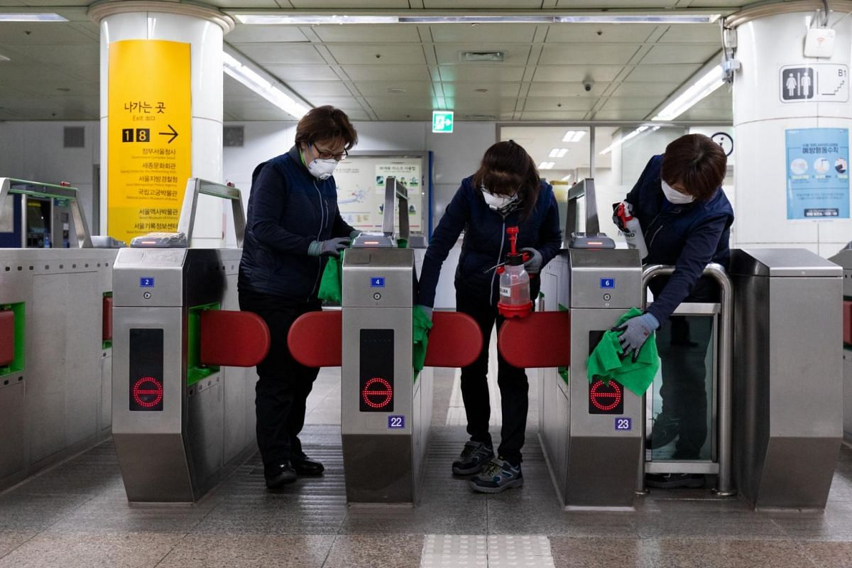 Workers spraying disinfectant and wiping fare gates inside the Gwanghwamun subway station in Seoul on Feb 3, 2020.