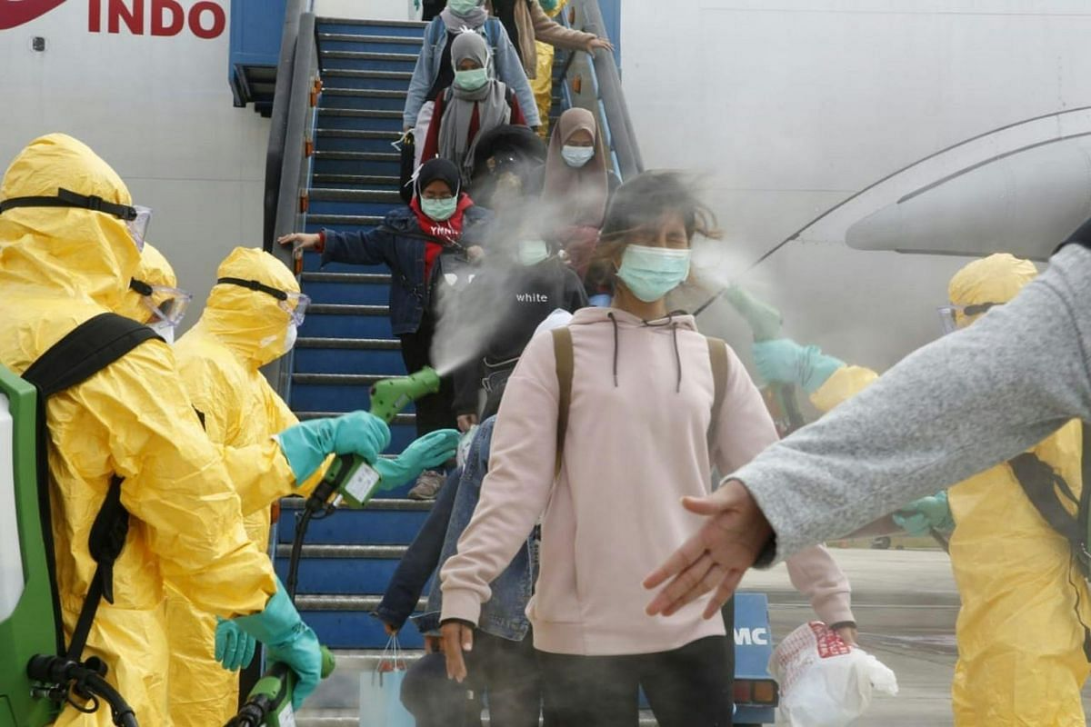 Officials disinfecting Indonesian students as they disembark from a plane upon arrival at Hang Nadim international airport in Batam on Feb 2, 2020, following their evacuation from Wuhan, China.