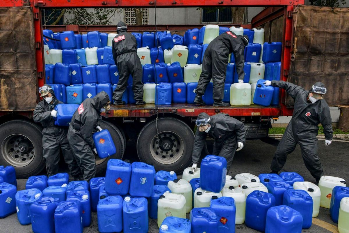 Chinese paramilitary police officers wearing protective gear transferring pails of disinfectant on  on Feb 12, 2020, in Yunmeng county, outside Xiaogan City in Hubei province.