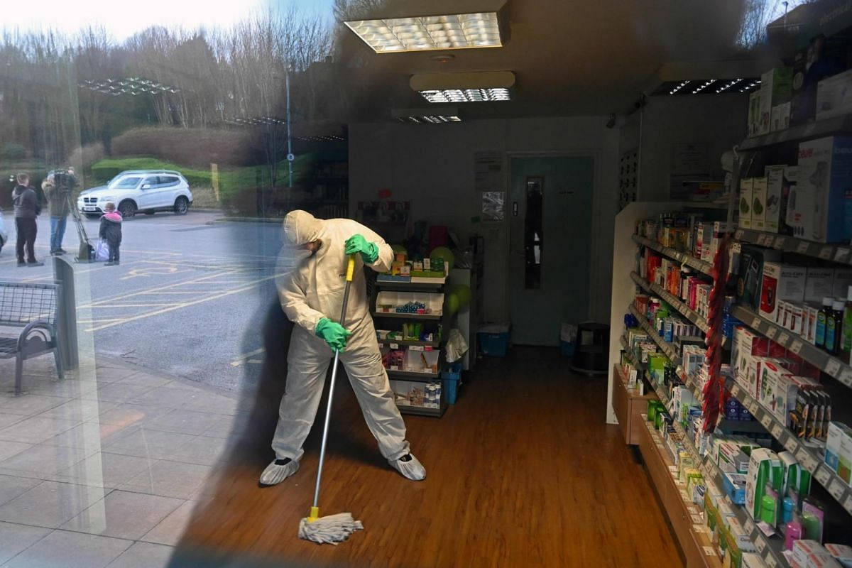 A worker in protective clothing, including face mask and gloves, cleaning the floor of the pharmacy attached to the The County Oak Medical Centre in Brighton, England, on Feb 10, 2020.