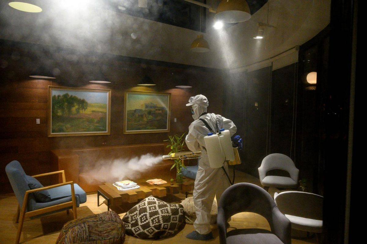 A worker in a protective suit using a fogging machine to disinfect a business establishment in Shanghai, on Feb 9, 2020.