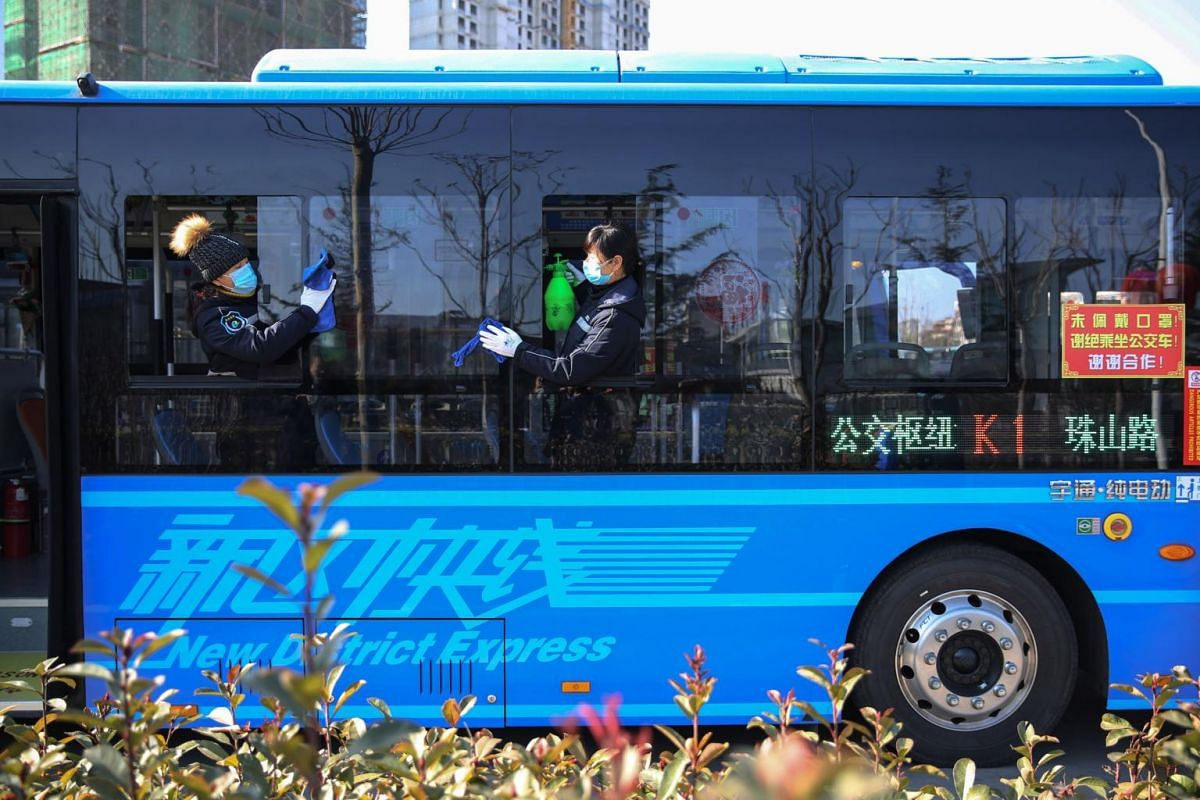 Employees disinfecting a bus in Qingdao, in China's eastern Shandong province, on Feb 5, 2020.