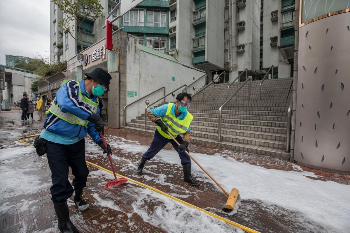 Workers cleaning a street outside the Whampoa Garden residential development in Hong Kong on Feb 4, 2020.