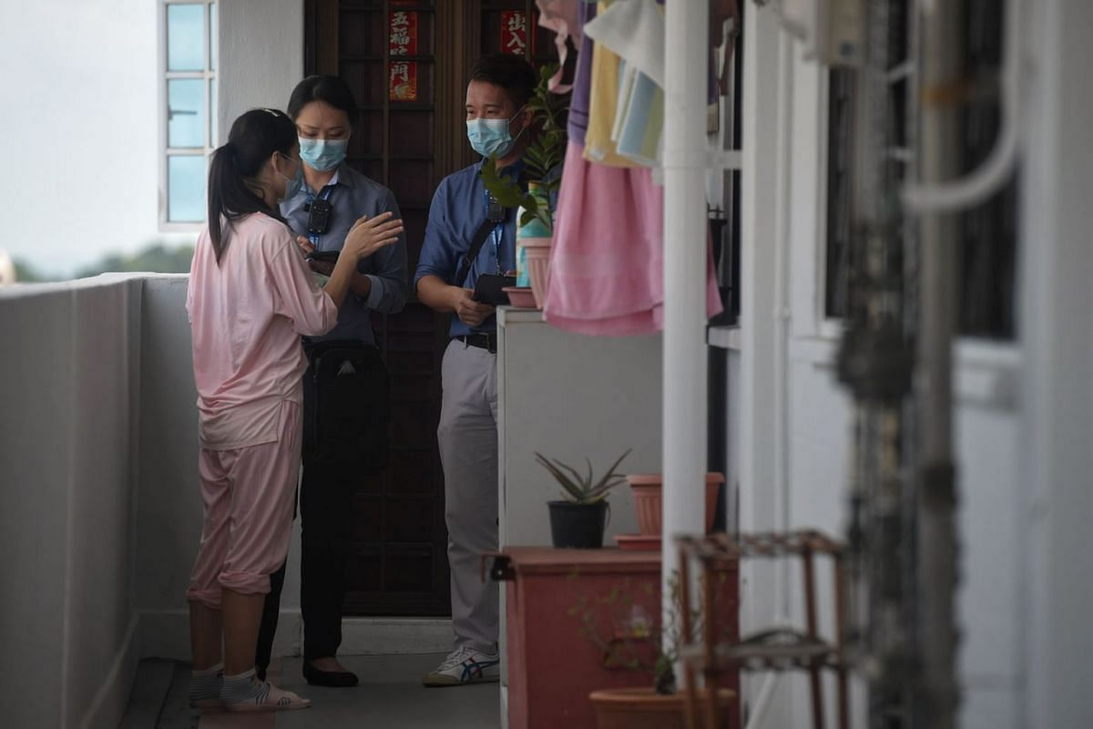 Mr Keith Aw, 41, and Ms Ong Peishi, 36, from the Ministry of Manpower's (MOM) foreign manpower management division, checking on a work pass holder who is nearing the end of her mandatory leave of absence (LOA) at her Bedok flat on Feb 12, 2020. PHO