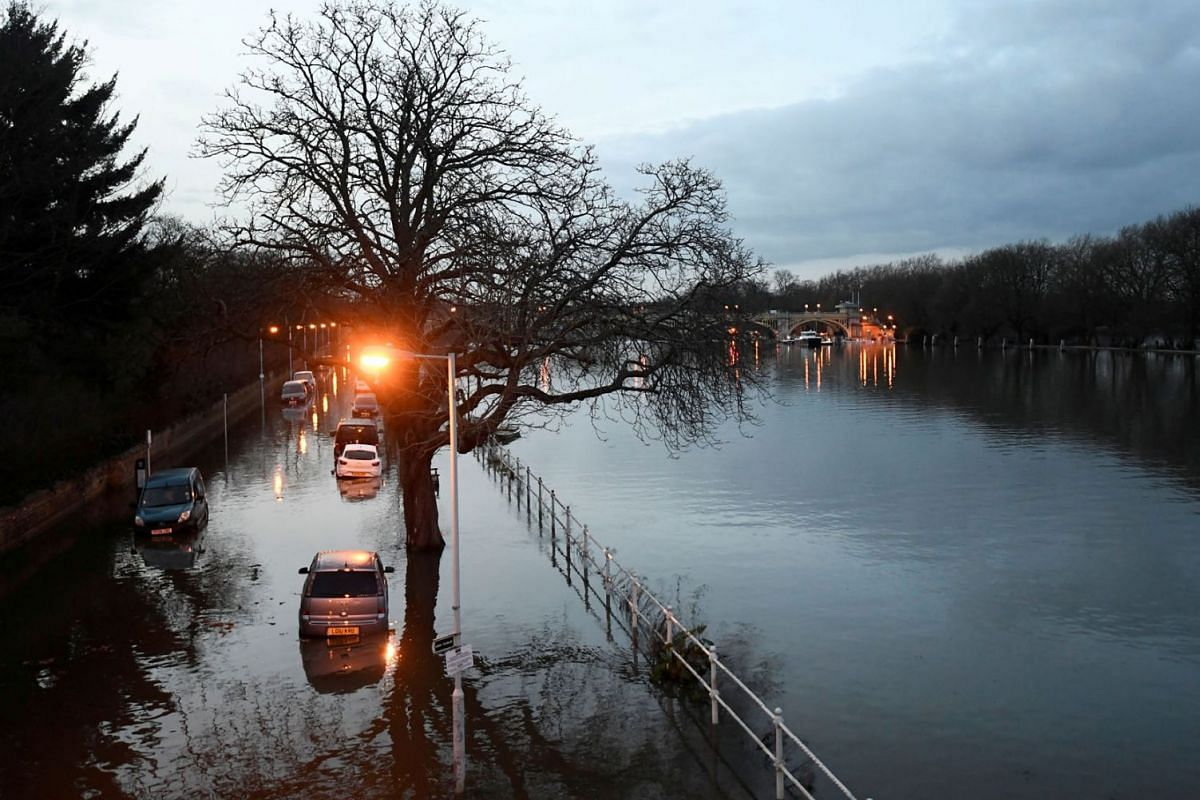 Cars are surrounded by water on a flooded road beside the River Thames in west London, Britain, February 12, 2020. PHOTO: REUTERS