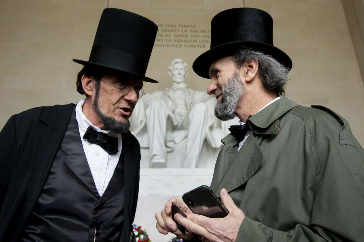 George Buss (L) of Freeport, Illinois and Greg Edwards (R) of Herndon, Virginia, speak with one another in front of the statue of Abraham Lincoln while they depict the sixteenth US President; during a ceremony to commemorate the anniversary of the bi