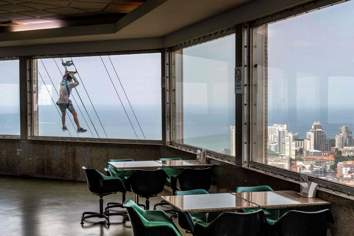 A tourist rides a zipline from the 55th floor of the observation tower of the Park Beach Resort in Pattaya on February 12, 2020. PHOTO:  AFP