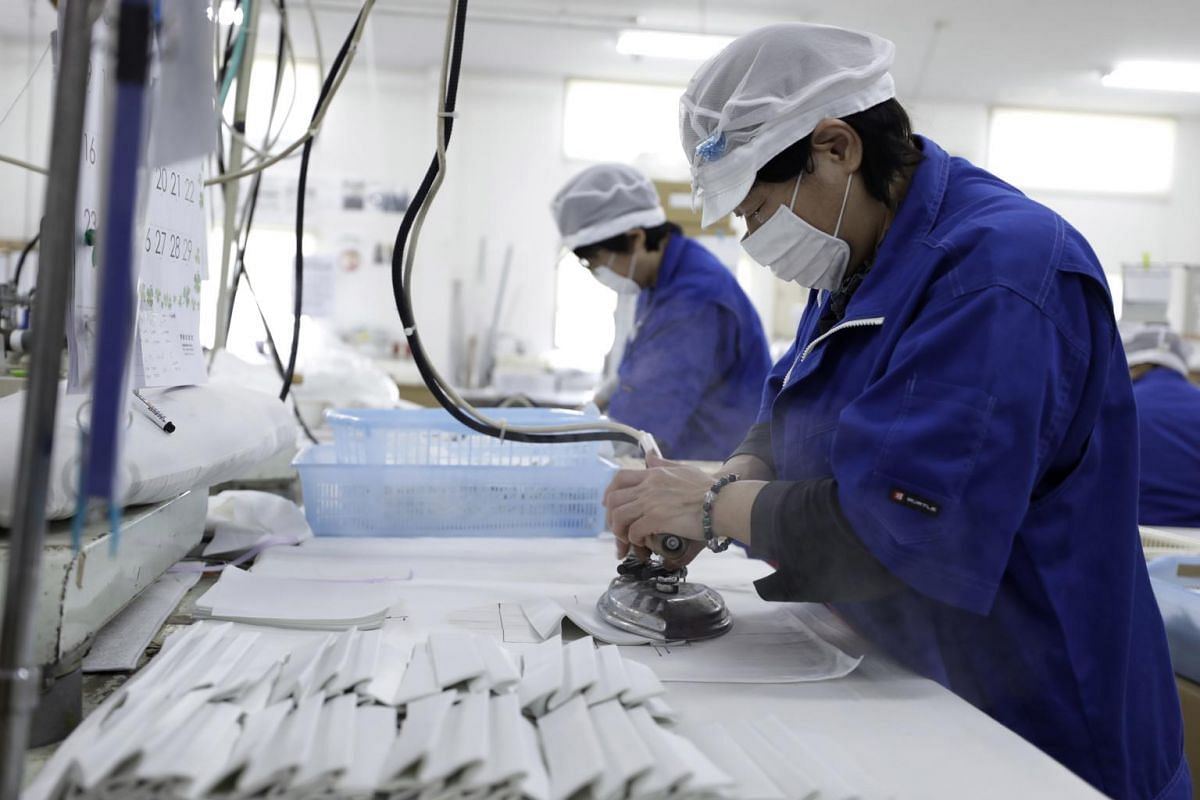 Employees work during the manufacturing of protective masks at the Clever Co. factory in Toyohashi, Japan, on Jan 31, 2020.