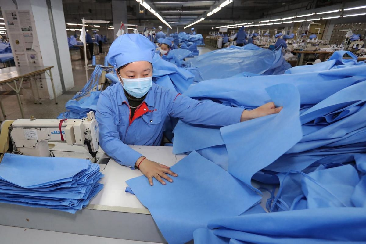 Workers producing isolation gowns in Zouping county, in east China's Shandong province, on Feb 10, 2020.