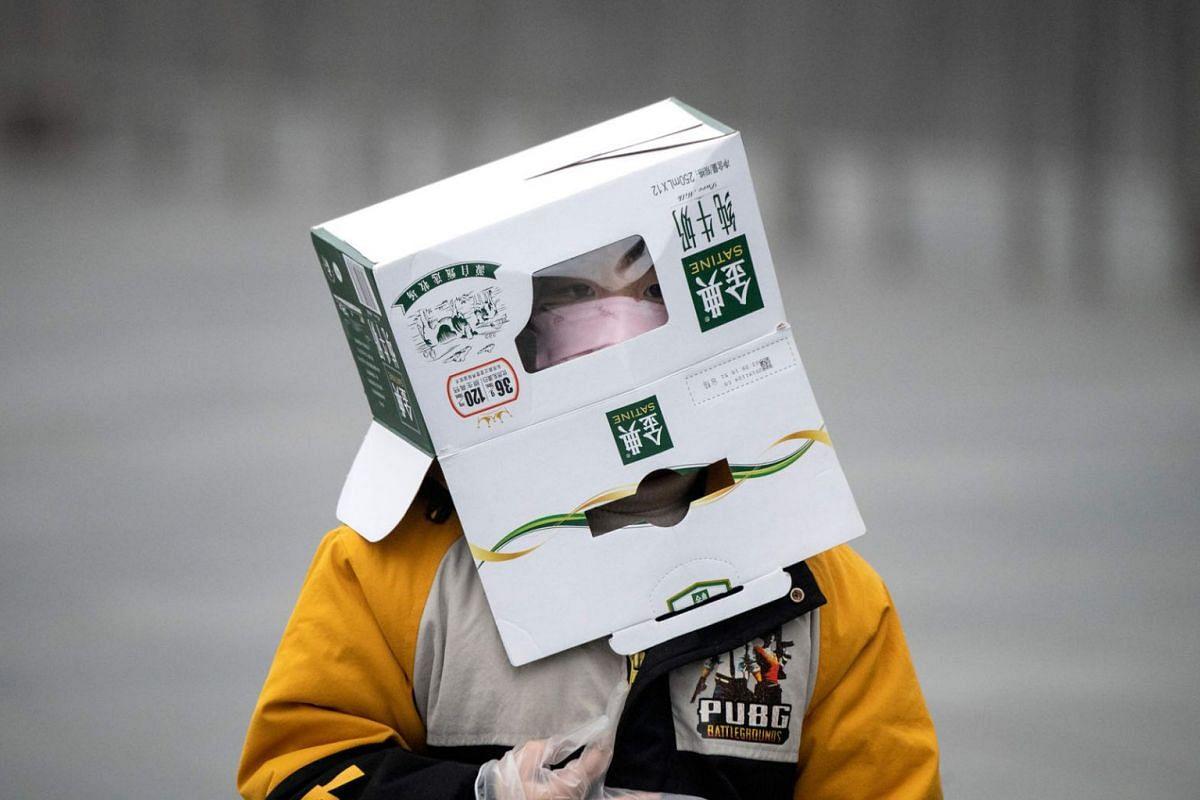 A boy wears a cardboard box on his head at the Shanghai Railway station in Shanghai on February 13, 2020. PHOTO: AFP