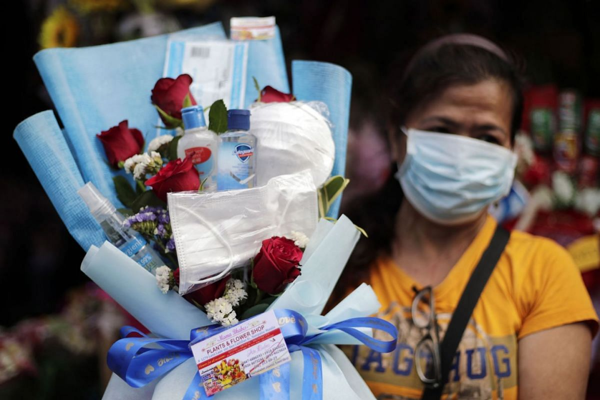 Vendor Monica Castro sells a bouquet of roses with facemasks and hygiene liquid bottles on the eve of Valentines day at a market in Manila, Philippines, February 13, 2020.PHOTO: EPA-EFE