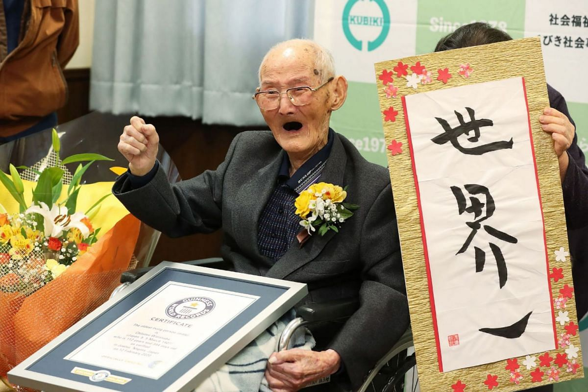 In this Japan Pool picture received via Jiji Press on February 12, 2020, 112-year-old Japanese man Chitetsu Watanabe poses next to calligraphy reading in Japanese 'World Number One' after he was awarded as the world's oldest living male in Joetsu, Ni