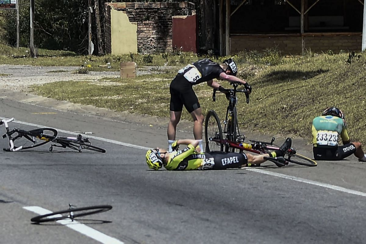 Cyclists of Illuminate's team Cameron Pipper (C-back), Efapel's Team Cesar Fonte (C-front) and Vinicios Rangel of Brazil's National team rest after crashing in the third stage of the Tour Colombia 2.1, in Tunja, Boyaca Department, Colombia, on Februa