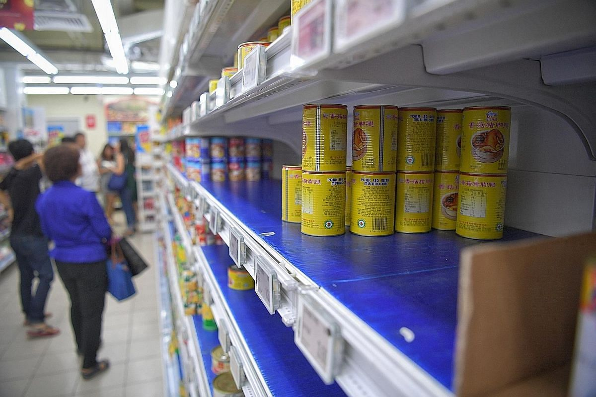 Shoppers bought up canned food (above) and stocked up on masks in the light of the coronavirus outbreak.