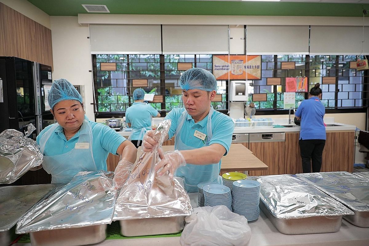 Left: Mr Soh helping Madam Lee Siew Eng, 88, to make her way from her home to the senior care centre. Right: Mr Soh preparing lunch for the centre's clients alongside colleague Khin Nyo Oo, 33. He says there is no difference in job duties between mal