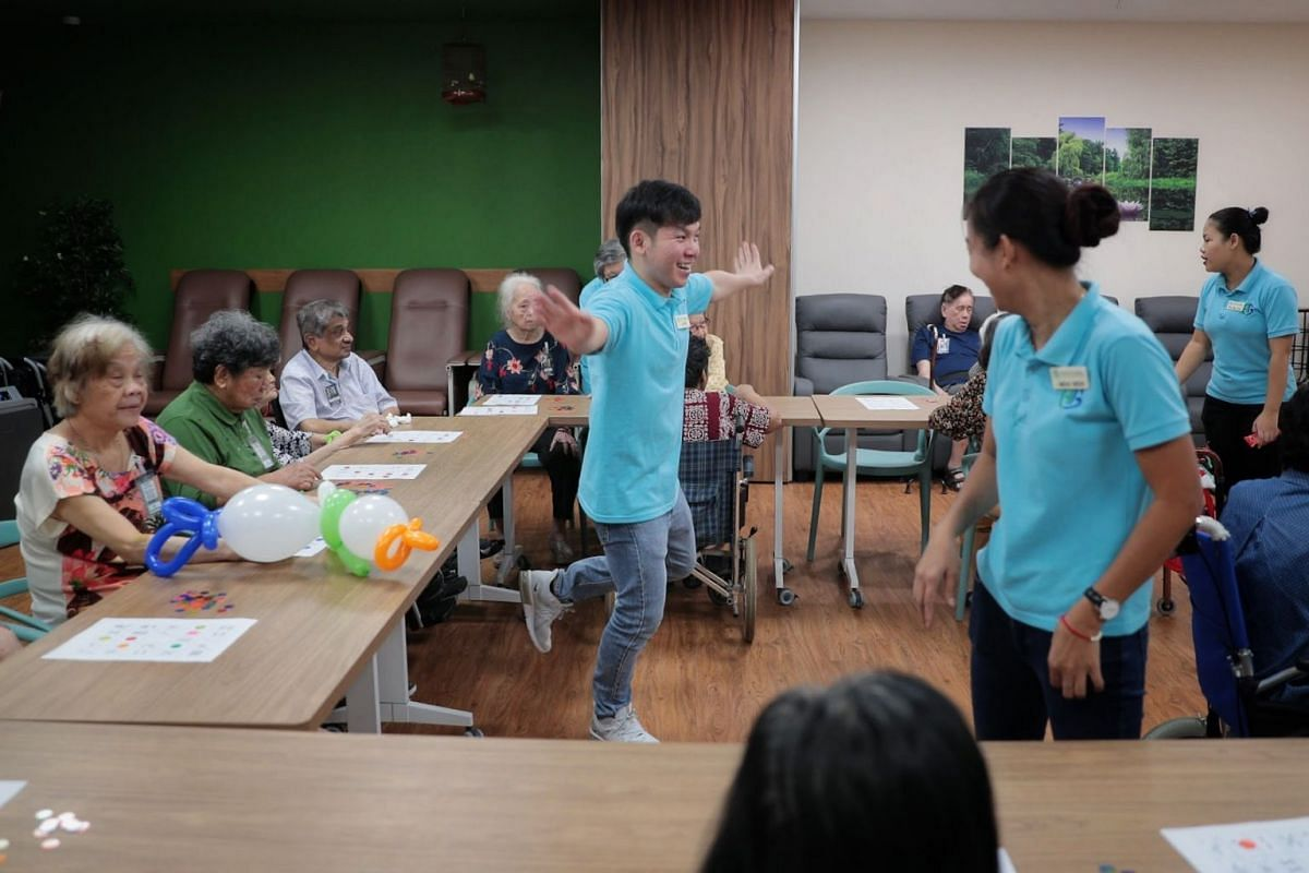 Mr Soh Jun Wei gestures as he conducts a game of bingo for the clients, drawing laughs from both clients and his colleagues.