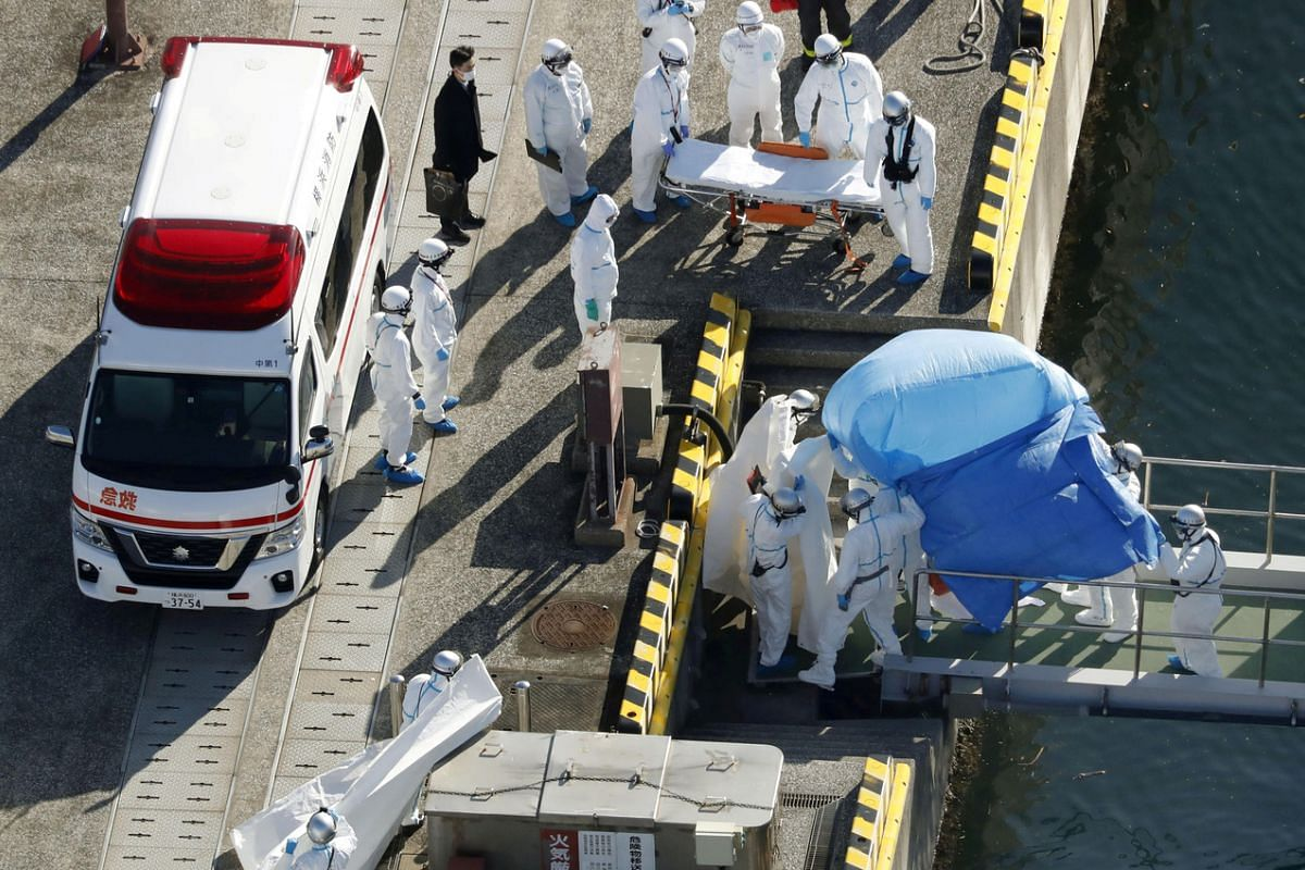 Officers in protective gear escorting a person off the cruise ship Diamond Princess who tested positive for the coronavirus in this photo taken by Kyodo on Feb 4, 2020.