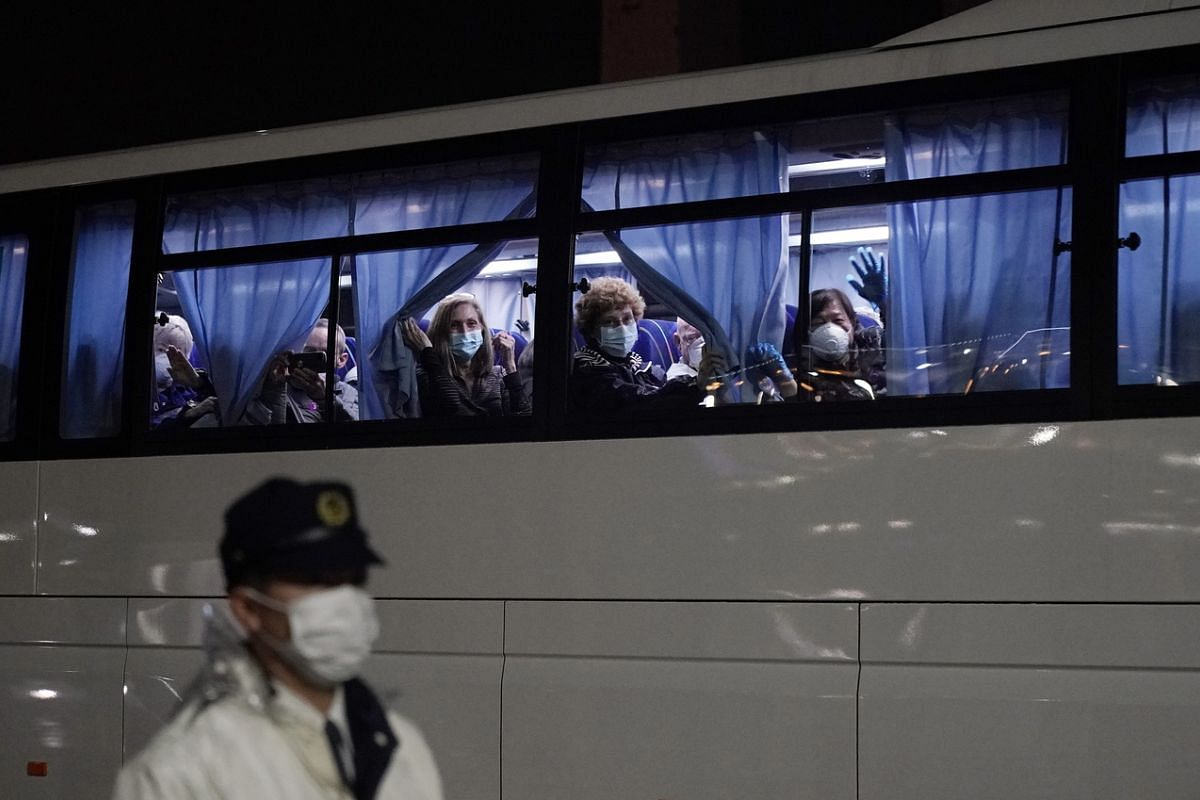 Former passengers leaving Daikoku Pier Cruise Terminal on a bus for repatriation on Feb 17, 2020.
