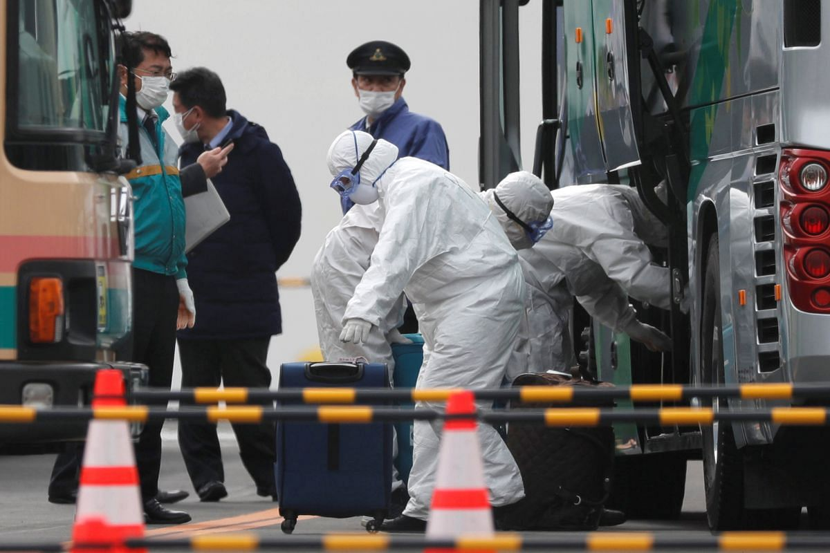 Workers loading luggage into a bus as a second group of passengers from the coronavirus-hit Diamond Princess cruise ship disembark in Yokohama on Feb 20, 2020.