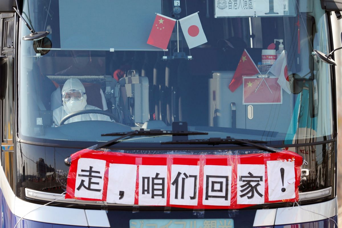 """A bus transporting Hong Kong passengers from the coronavirus-hit cruise ship Diamond Princess leaving the Daikoku Pier Cruise Terminal on Feb 21, 2020. The banner on the bus reads """"Go, let's go home together""""."""