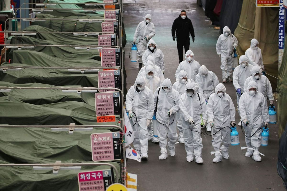 Market workers wearing protective gear spray disinfectant at a market in the southeastern city of Daegu on February 23, 2020 as a preventive measure after the COVID-19 coronavirus outbreak. PHOTO: YONHAP VIA AFP