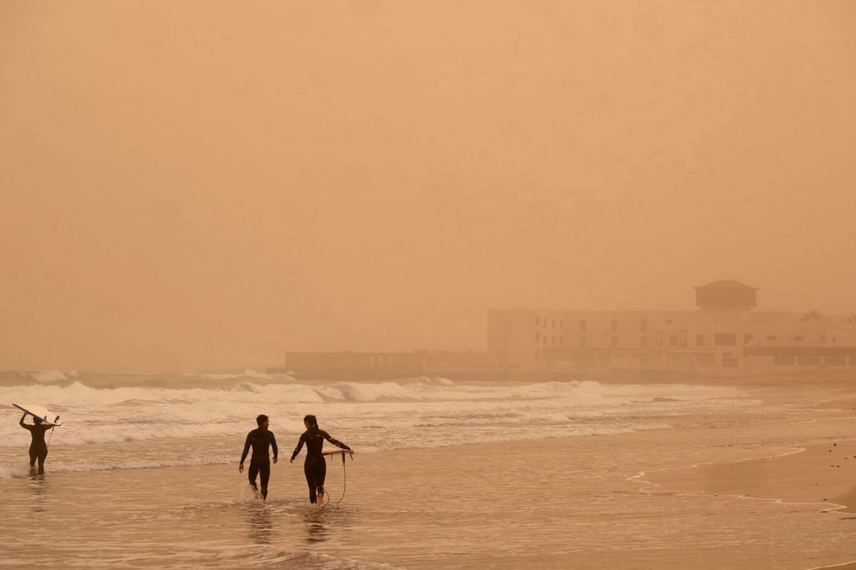 Surfers go for a swim at Playa Blanca in Puerto del Rosario, Fuerteventura, Canary Islands, Spain, February 23, 2020. Big amounts of dust and sand from Sahara desert made their way into the islands the day before. PHOTO: EPA-EFE